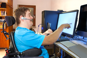 Man interacting with computer using assistive technology