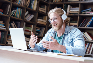 man with headphones talking into laptop