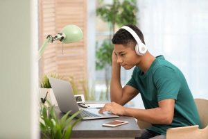 boy in green shirt at laptop