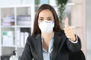 Executive with mask with thumbs up looking camera