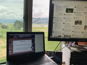 Two screens in front of a window overlooking a mountain range, each screen has OLC Ideate programming on it, and one has Twitter up as well