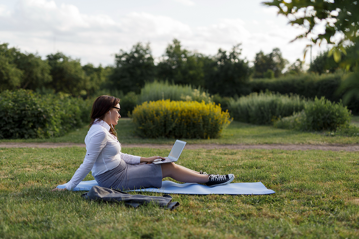 Woman working on laptop at park