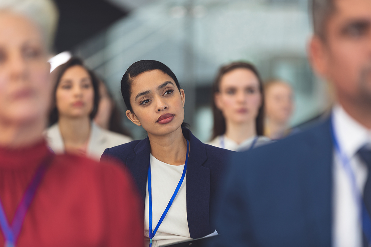 Photograph of woman listening intently at a conference